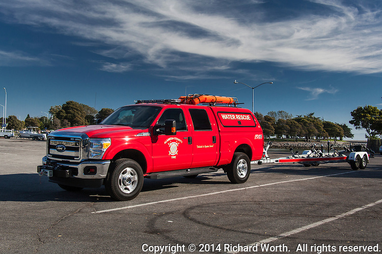 A big red Alameda County Fire Department truck with an empty boat trailer at the San Leandro Marina Boat Launch.