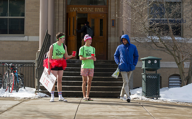 """Feb. 11, 2015; Siegfried residents, Ivan Finkelstein (finance major) and Henry Long (engineering major) (right) stand outside La Fortune to collect donations for the """"Day of Man,"""" a fundraiser for the South Bend Center for the Homeless. Siegfried residents wear shorts and t-shirts in cold weather to show solidarity with the homeless. (Photo by Barbara Johnston/University of Notre Dame)"""