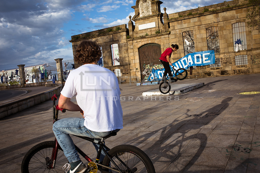 Roberto and his friend Brandán bike in front of the Navantia shipbuilding compound. Ferrol, Spain.