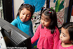 Education preschool 4-5 year olds three girls playing with computer