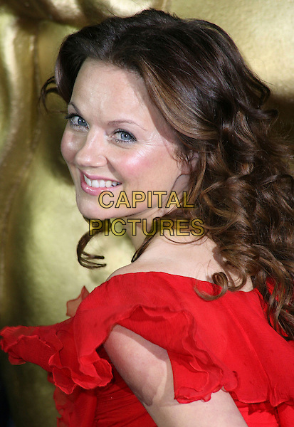 GERI HALLIWELL .British Academy Children's Film and Television Awards at the London Park Lane Hilton, Park Lane, England, UK, November 30th 2008..BAFTA BAFTA's portrait headshot red looking back over shoulder brunette curly hair smiling .CAP/JIL.©Jill Mayhew/Capital Pictures