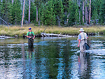 A man and a woman fish in the Firehole River in Yellowstone National Park.