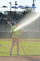 The grounds crew waters the field as the Ogden Raptors prepared to face the Great Falls Voyagers in Pioneer League play at Lindquist Field on August 14, 2013 in Ogden Utah. (Stephen Smith/Four Seam Images)