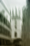 The abstract blurred tower of a historic building in London between modern office buildings.
