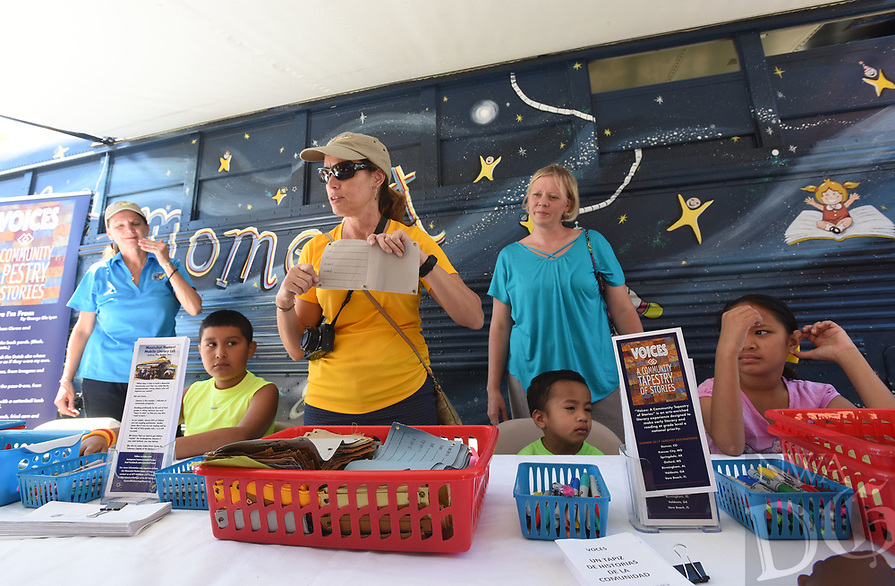NWA Democrat-Gazette/FLIP PUTTHOFF <br /> Marie O'Brien (center) and Jenny Oesterle (right), assistant principal at Parson Hills Elementary, get students started on art projects Wednesday at the Springdale school, at The Moonshot Rocket Bus.