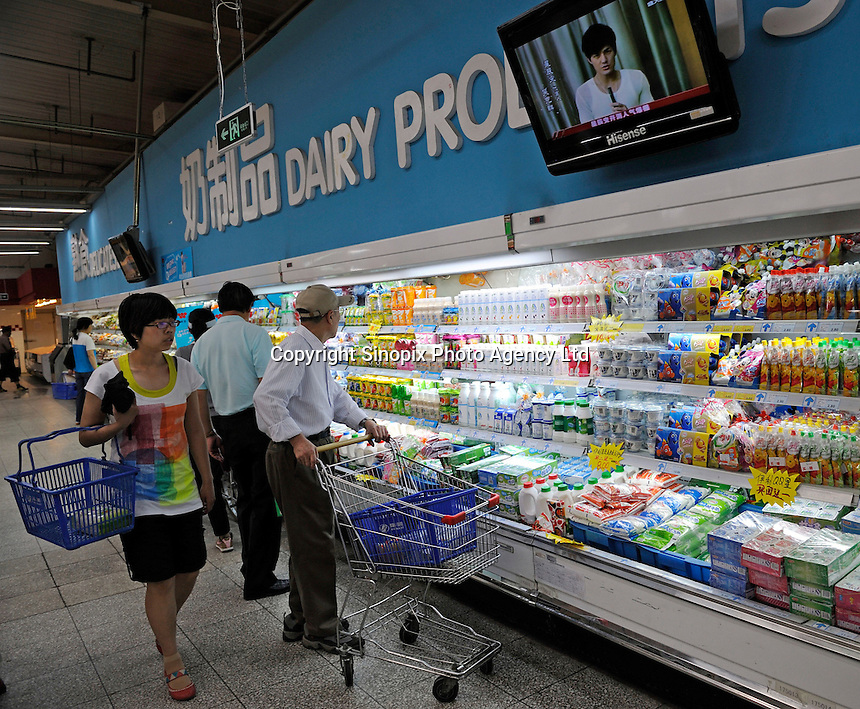 Chinese customers buying dairy products at a Wu Mart supermarket in Beijing, China.  Wu Mart, the Beijing-based chain, was founded in the early 1990s by Zhang Wenzhong. Its name smacks of the fame of U.S. retail giant Wal-Mart. Wu Mart and Wal-Mart are competing in different arenas and each appears to be going after a different class of consumer. By 2005, Wu Mart had more than 450 hypermarkets, supermarkets and convenience stores, and is one of only a few Chinese retailers whose shares are publicly traded..28 May 2011