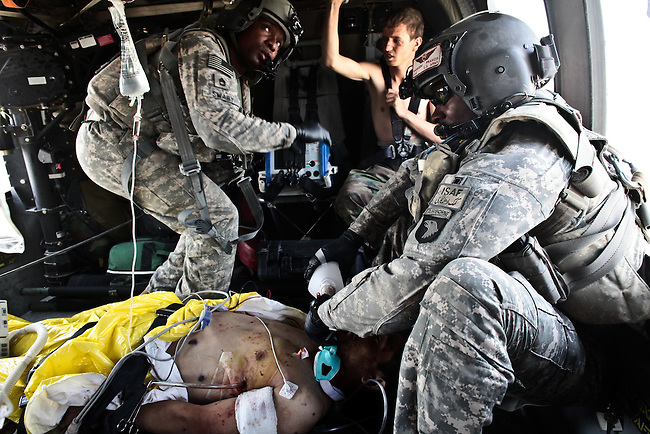 "Flight medic Staff Sgt. Rakheem Francis, 24, of Queens, N.Y., (right) and crew chief Sgt. 1st Class Lloyd Swaby, 36, of Fort Lauderdale, Fla. (left), with the 101st Combat Aviation Brigade's ""Shadow Dustoff,"" treat an Afghan soldier who was severely wounded in a Taliban ambush near Kandahar, Afghanistan. The soldier died a short time later. Sept. 19, 2010. DREW BROWN/STARS AND STRIPES"
