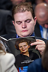 © Joel Goodman - 07973 332324 . No syndication permitted . 29/09/2013 . Manchester , UK . A member of the audience reads a Margaret Thatcher tribute . Day 1 of the Conservative Party Conference at Manchester Central . Photo credit : Joel Goodman