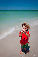 YOung boys holds handful of shells on beach along Gulf of Mexico. Photo by Debi Pittman Wilkey