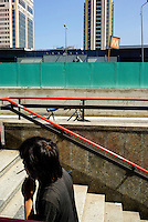 "Milano, quartiere Garibaldi, progetto di riqualificazione dell'area di Porta Nuova. Un uomo con una sigaretta sale la scalinata della metropolitana con la stazione e le Torri sullo sfondo --- Milan, Garibaldi district,  requalification project of ""Porta Nuova"" area. A man with a sigarette climbing the stairs of the subway with the station and the Towers on the background"