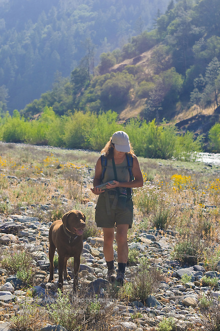 Woman hiking with her dog, along the North Fork of the American River, Weimar, California.