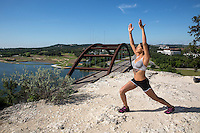 Attractive healthy young african-american athlete woman performs yoga stretches on the 360 Bridge overlook cliff on Lake Austin, Texas.