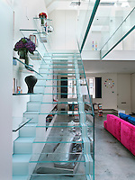 Minimal glass shelving appears to hover on the wall of the glass staircase leading up to the mezzanine
