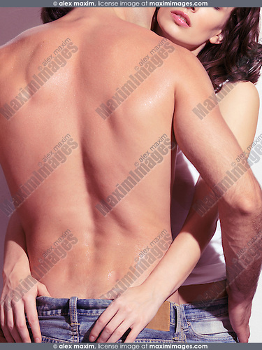 Young woman embracing a man with bare torso, closeup of back, rear view.