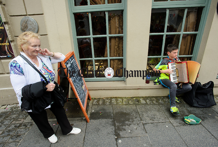 A woman listens to the sounds of Cormac Mc Colgan of Donegal as he plays  on O Connell street, Ennis during Fleadh Cheoil na hEireann. Photograph by John Kelly.