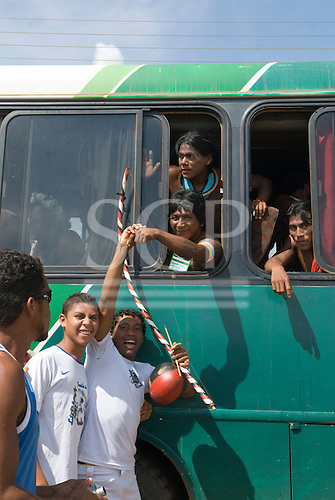 "Altamira, Brazil. ""Xingu Vivo Para Sempre"" protest meeting about the proposed Belo Monte hydroeletric dam and other dams on the Xingu river and its tributaries. Kayapo Indian warrior say goodbye to young people from a bus."