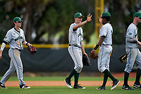 Dartmouth Big Green Trevor Johnson (28), Kolton Freeman (28), and Blake Crossing (13) celebrate closing out a game against the Omaha Mavericks on February 23, 2020 at North Charlotte Regional Park in Port Charlotte, Florida.  Dartmouth defeated Omaha 8-1.  (Mike Janes/Four Seam Images)