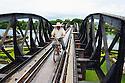 Man rides bike across the bridge over the river Kwai, Death Railway, Kanchanaburi, Thailand