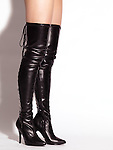 Closeup of legs of a woman wearing sexy black leather thigh high stiletto boots