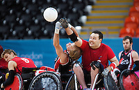 18 APR 2012 - LONDON, GBR - Great Britain's Ross Morrison (GBR) (Class 2.5) (second from right in red) beats Canadian Garett Hickling (CAN) (Class 3.5) (second from left) to the ball during their London International Invitational Wheelchair Rugby Tournament match at the Olympic Park Basketball Arena in Stratford, London, Great Britain (PHOTO (C) 2012 NIGEL FARROW)