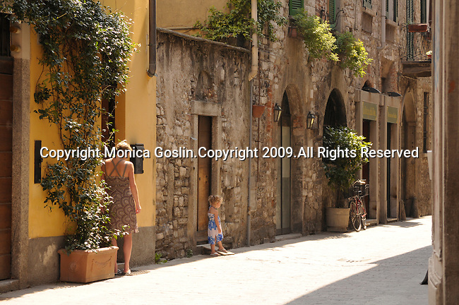 A girl in a blue and white sundress and her mother in a brown sundress, stand in the sun and look down a street in Como on Lake Como, Italy.