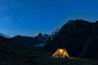 Tent camp at night. Mount Igikpak is the highest peak in the Schwatka Mountains region of the Brooks Range, Gates of the Arctic National Park, Alaska