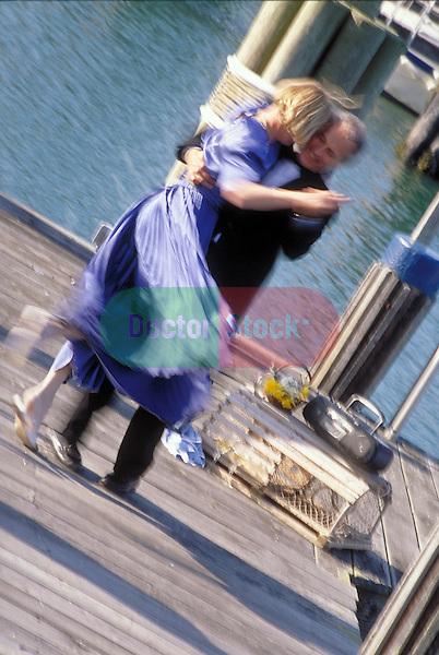 dressed-up couple dances on dock