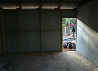 "Koh Lanta, Thailand--A concrete worker can be seen through the door of one of World Vision's new government-sponsored temporary structures.  The 12'x12' units were built to house residents from the village of Hua Laem on Koh Lanta island, Thailand, who lost their homes to the Tsunami.  Villagers, however, strongly oppose moving and are beginning to rebuild their homes.  The development, which villagers call the ""hog farm"", is made up of single-room units that are hot and lack any kind of privacy.  To make matters more complex, Hua Laem is primarily a Muslim community and the units are built on property owned by a Buddhist temple.  Villagers also fear that the government's motive for moving them is financial as the land they've occupied for over a hundred years is valuable ocean-front property which, rumor has it, the government wants to develop into a marina.  01/20/05 © Julia Cumes / The Image Works"