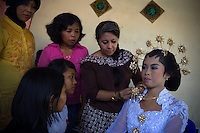 Rossy, one of the 'Twin Teachers', shows villagers from a remote village in Indonesia's Lampung province how to apply make up to a model bride as part of wedding production training. Aside from the training itself, the villagers also get to keep the wedding gowns and make-up  donated by the twins as start-up capital for their business. The trials and tribulations of the twin sisters' crusade has not deterred their passion for work. Instead, they have expanded to various parts of the country promoting training modules to gain practical skills as part of their adult education programme targeting women empowerment. Since the early 1990s, twin sisters Sri Rosyati (known as Rossy) and Sri Irianingsih (known as Rian) have used their family inheritance to set up and run 64 schools in different parts of Indonesia, providing primary education combined with practical skills to some of the country's most deprived children.