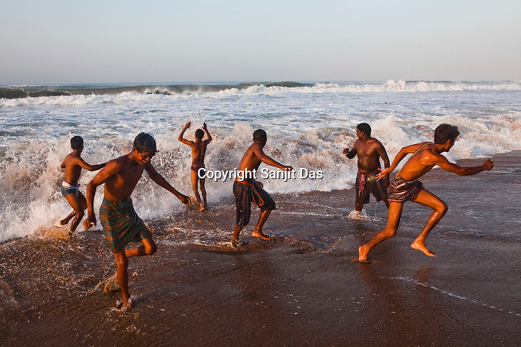 Tourists run as the wave crashes on the shores of Puri Beach along the Bay of Bengal in Puri, Orissa, India. A dip in its salty waters is believed to hold great religious significance, as a result these golden sand beaches sees is a never-ending rush of pilgrims and tourists. Photo: Sanjit Das/Panos