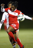 BOYDS, MARYLAND - April 06, 2013:  Jasmyne Spencer (20) of The Washington Spirit is tackled from behind by Morgan Stith (4) of the University of Virginia women's soccer team in a NWSL (National Women's Soccer League) pre season exhibition game at Maryland Soccerplex in Boyds, Maryland on April 06. Virginia won 6-3.
