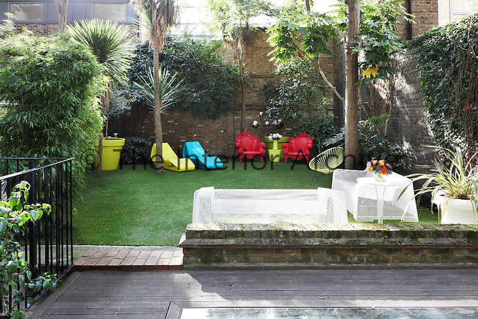 The walled garden has an eclectic mix of colourful contemporary garden chairs, which are set out on a lawn of artificial grass