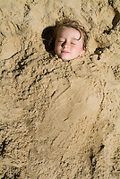 Child buried in the sand at the beach, Biscarrosse, France.
