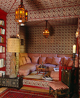 This library has been given a Moroccan flavour by a raised sitting area furnished with a comfortable banquette and walls and ceiling tented with paisley fabric