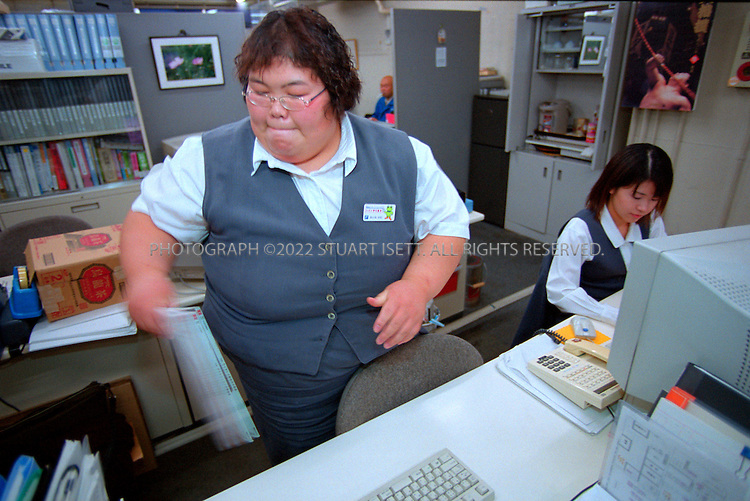 10/26/2001--Hirosaki, Aomori Prefecture, Japan..Rie Tsuihiji, 23, Japan's leading female sumo wrestler and 2000 world champion, at work in Osaka. Tsuihiji works at a Japanese trading firm as a typical 'OL' or office lady...All photographs ©2003 Stuart Isett.All rights reserved.This image may not be reproduced without expressed written permission from Stuart Isett.
