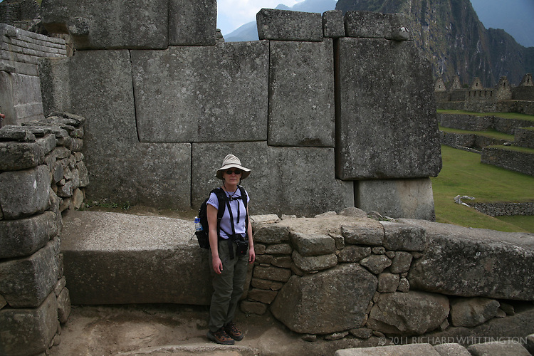 A tourist stands in front of stonework at Machu Pichu, where some of the stone blocks are estimated to weigh as much as 300 tons.