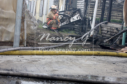 A fire chief on a radio talking to firefighters on a fire scene