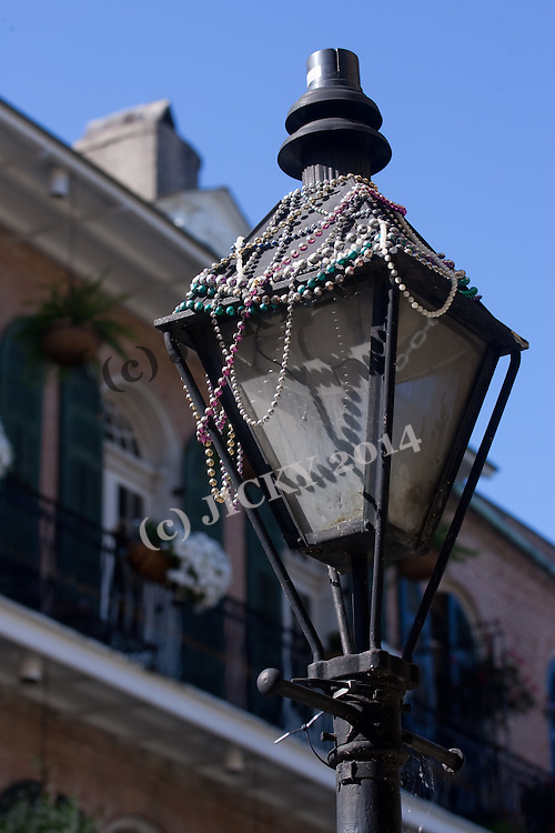 Street lamp on Royal covered with Mardi Gras beats
