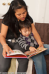Two year old toddler boy with mother read to pointing at picture