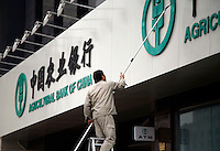 A man cleans the sign of a Agricultural Bank of China in Shanghai, China..