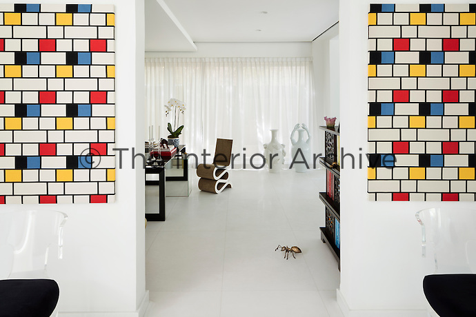 A view through an open doorway into the home office with a Wiggle chair by Frank Gehry and two white vases by Pois Potten. The colourful artworks bring splashes of colour to the white beackground.