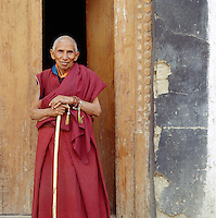 Mature monk in a monastery doorway, Ladakh, India