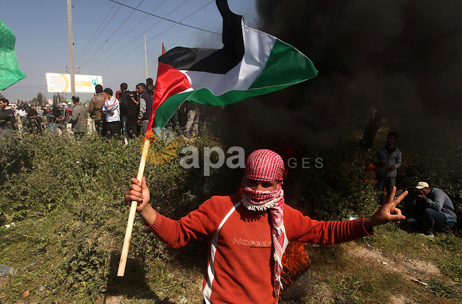 Palestinian protesters shout during a protest marking Land Day, near the border between Israel and the northern Gaza Strip March 30, 2012. Israeli security forces fired rubber bullets, tear gas and stun grenades to break up groups of Palestinian stone-throwers on Friday as annual Land Day rallies turned violent. Land Day commemorates the killing by security forces of six Arabs in 1976 during protests against government plans to confiscate land in northern Israel's Galilee region. Photo by Ashraf Amra