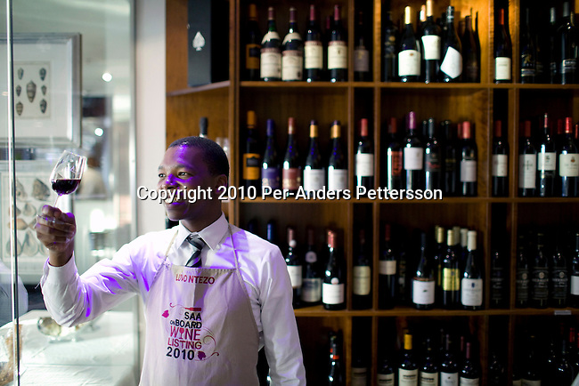 CAPE TOWN, SOUTH AFRICA - MARCH 23: Luvo Ntezo, a wine sommelier at the Twelve Apostles Hotel, stands with a glass of red wine in a wine cellar on March 23, 2010 in Cape Town, South Africa. Mr. Ntezo grew up in difficult conditions and got a luck break working at a Cape wine farm where he learned about wines. His talent was spotted and he went through many wines courses. He is now an award winning sommelier at Twelve Apostles Hotel, one of the best hotels in South Africa. (Photo by Per-Anders Pettersson/Getty Images)