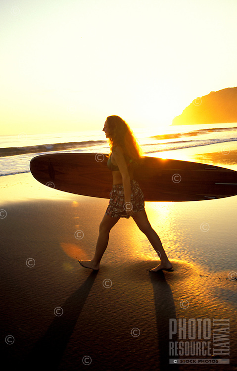 Woman going out surfing at sunset in Waipio Valley