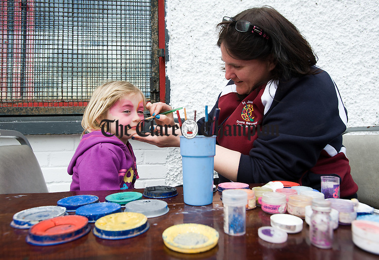 Aoibhinn Mc Grath gets her face painted by Therese Wall during the Ennis Rugby Club family fun day at the Show grounds. Photograph by John Kelly