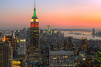 View looking south at twilight from the Top of the Rock including the Empire State Building, illuminated in Red/White/Green in honor of Columbus Day, and other Manhattan skyscrapers.  The rising Freedom Tower at the World Trade Center can be seen on the horizon to the right of the Empire State Building.