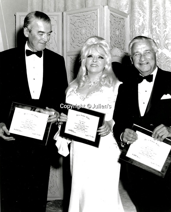 """BNPS.co.uk (01202 558833)<br /> Pic:  Julien's/BNPS<br /> <br /> A plaque presented to Mae West in April 1968 granting her membership to the Division of Cinema at the University of Southern California.  West accepting the Delta Kappa Alpha plaque with Jimmy Stewart and Melvyn LeRoy.<br /> <br /> A selection of trailblazing 1930s starlet Mae West's most recognisable film costumes have emerged for sale for £320,000. ($400,000)<br /> <br /> The auction features the actress and screenwriter's gowns, headdresses and tiaras, as well as props from her films and her scripts.<br /> <br /> West, a New York native, was the Marilyn Monroe of her era, earning a 'bad girl' reputation for starring in risque productions.<br /> <br /> She famously coined the phrase: """"When I'm good, I'm very good, but when I'm bad, I'm better."""""""