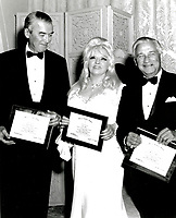 "BNPS.co.uk (01202 558833)<br /> Pic:  Julien's/BNPS<br /> <br /> A plaque presented to Mae West in April 1968 granting her membership to the Division of Cinema at the University of Southern California.  West accepting the Delta Kappa Alpha plaque with Jimmy Stewart and Melvyn LeRoy.<br /> <br /> A selection of trailblazing 1930s starlet Mae West's most recognisable film costumes have emerged for sale for £320,000. ($400,000)<br /> <br /> The auction features the actress and screenwriter's gowns, headdresses and tiaras, as well as props from her films and her scripts.<br /> <br /> West, a New York native, was the Marilyn Monroe of her era, earning a 'bad girl' reputation for starring in risque productions.<br /> <br /> She famously coined the phrase: ""When I'm good, I'm very good, but when I'm bad, I'm better."""