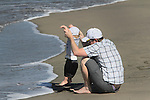 A dad and child cool there feet on the shores of Crissy Field during a air show by the Navy Blue Angels.